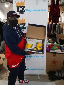 man holding yellow sneakers with ezshopz banner behind