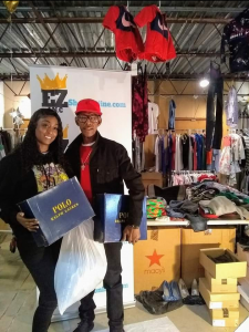 couple posing with red hat with ezshopz behind