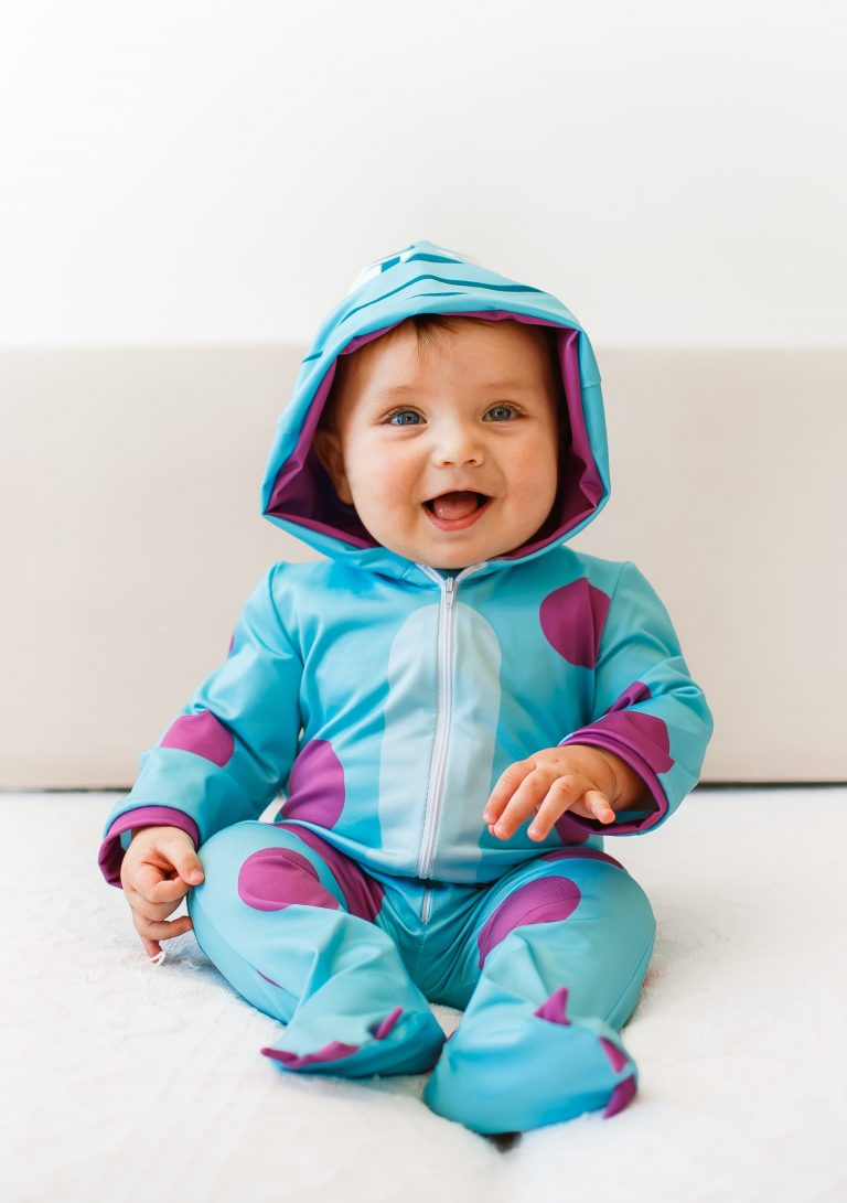 infant boy smiling on bed in blue pyjama