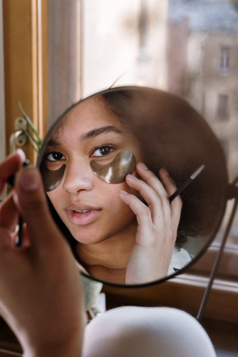 girl looking at mirror with mask under her eyes