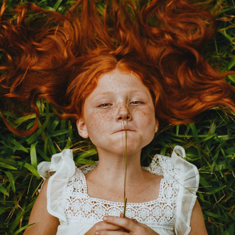 red hair girl on grass in white dress