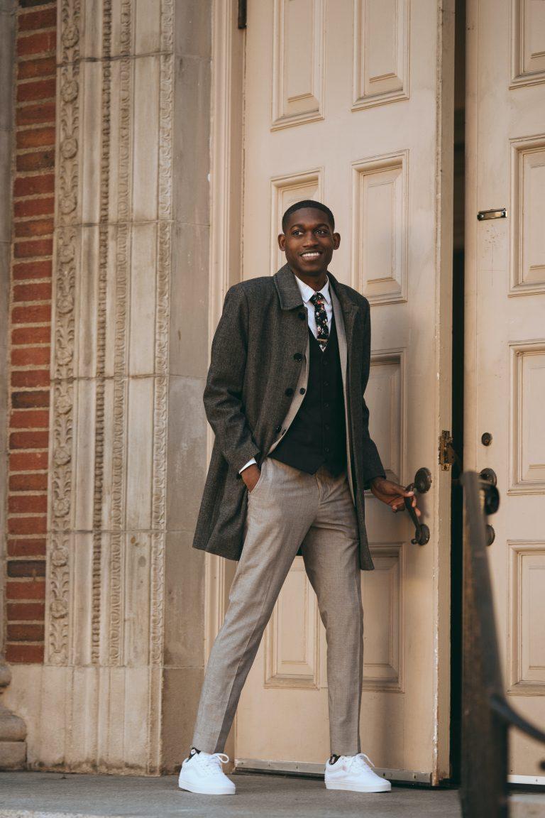 man standing opening the door in white sneakers and coat