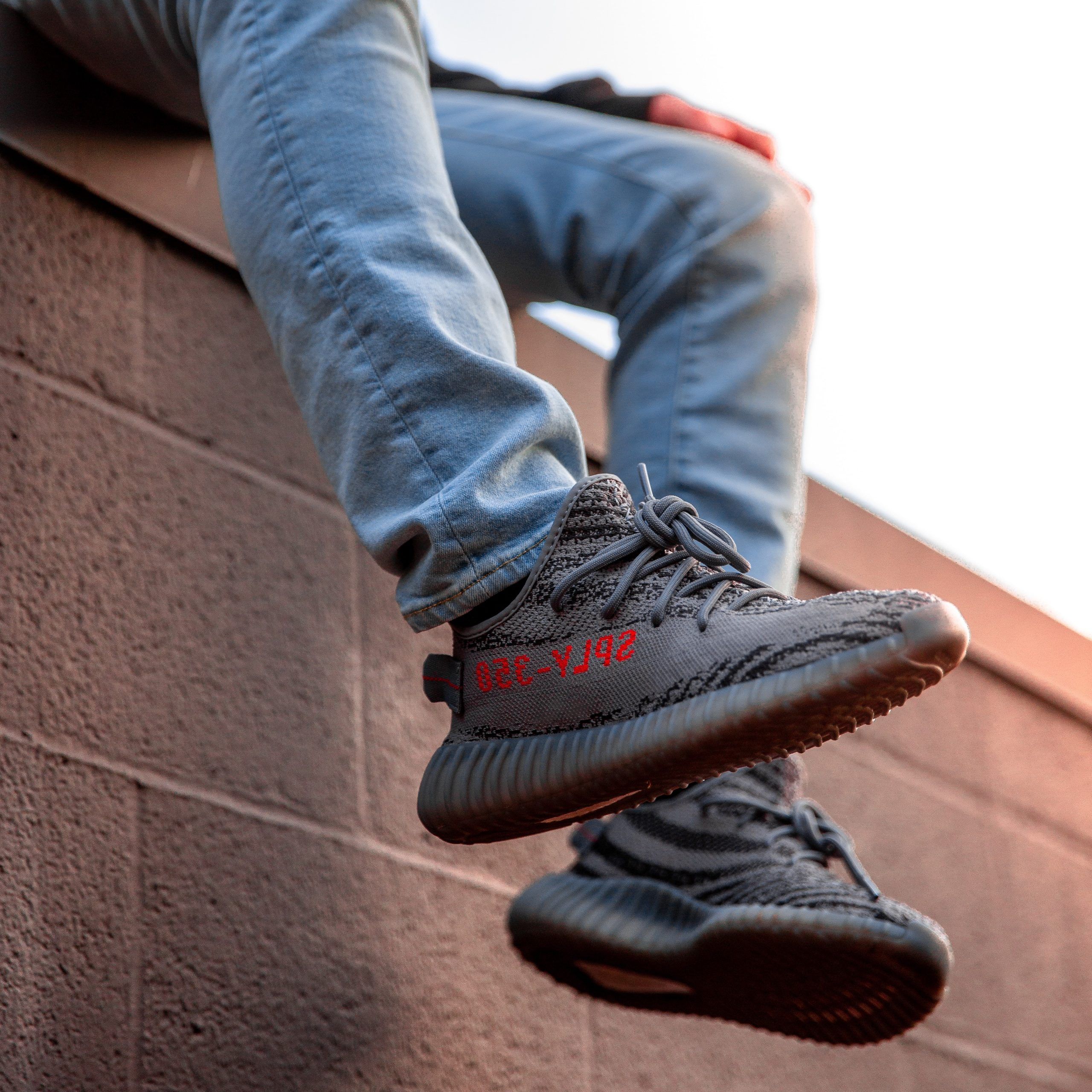 man sitting on ledge with his feet hanging in gray sneakers