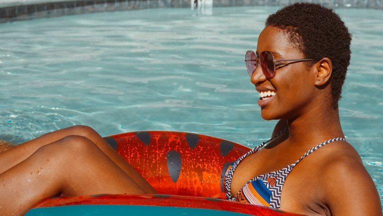 dark skin woman in the pool smiling
